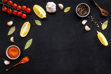 Kitchen frame with spices and food - pepper, garlic, cherry tomatoes - on black background top-down frame.