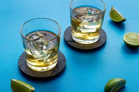 Whiskey with ice. To glasses of strong alcohol drink near lime on blue background. Reklamní fotografie