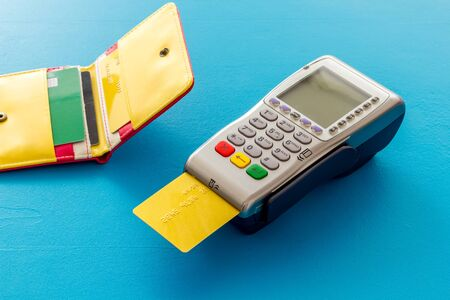 Bank terminal for payments and plastic card on blue background.