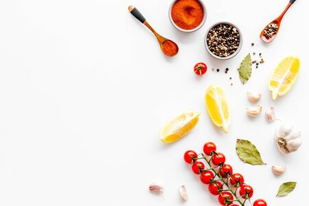 Cooking background with spices and vegetables - pepper, garlic, bay leaf, cherry tomatoes - on white desk top-down.