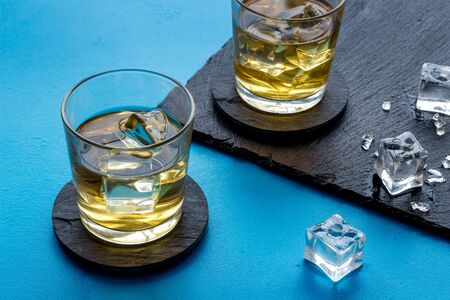 Whiskey near ice cubes on blue background.