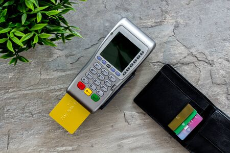 Pay by credit card in shop. Terminal and card on grey stone background top-down.