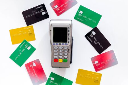Bank terminal for payments among plastic cards on white background top-down. Stock Photo