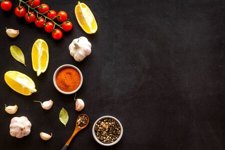 Cooking background with spices and vegetables - pepper, garlic, cherry tomatoes - on black desk top-down frame.