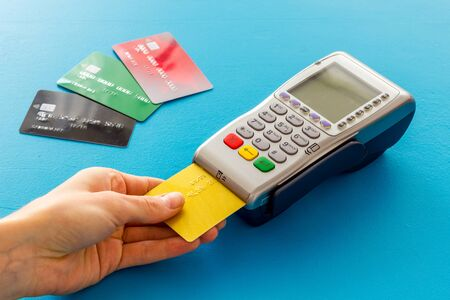 Payments in shops. Hand insert bank card in terminal on blue background. Stock Photo