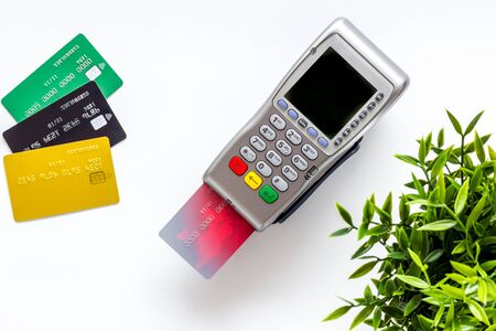 Pay by credit card in shop. Terminal and card on white background top-down.