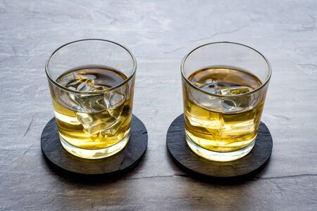 Whiskey with ice. To glasses of strong alcohol drink on grey stone background.
