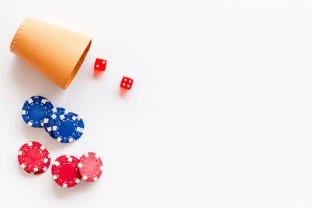 Poker concept. Chips, dices, cup for dice on white background top-down copy space