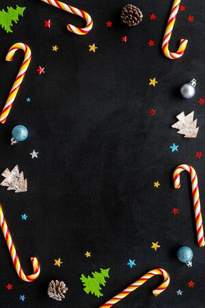 New Year greeting card design. Christmas candy cane, tree and balls on black background top-down frame copy space Stock Photo
