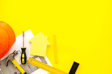 Construction concept. Helmet, instruments, blueprints on yellow background top-down frame copy space