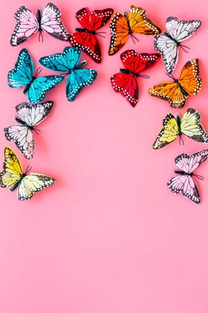 Multicolored tropical butterflies on pink background top-down frame copy space