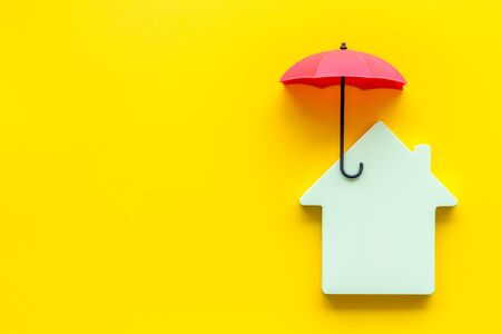 House insurance concept. Toy house defended by umbrella on yellow backgound top view copy space Imagens