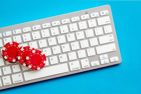 Gambling, online games. Chips near keyboard on blue background top-down Banque d'images