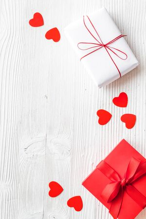 Present to a lover on Valentines Day. Gift boxes near paper hearts on white wooden background top-down frame copy space Reklamní fotografie
