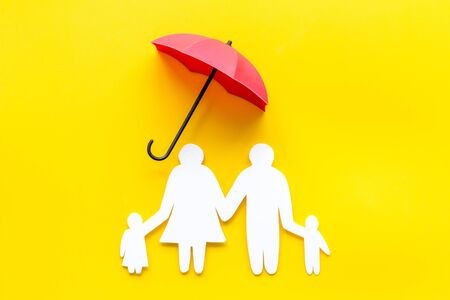 Health protection concept. Family cutout under umbrella on yellow background top-down. Stockfoto