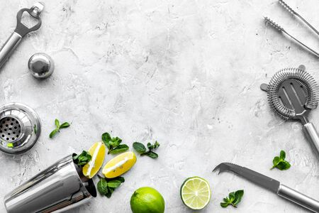 Bar background. Tools, ingredients for making cocktails. Shaker, lime, ice on grey background top-down frame copy space