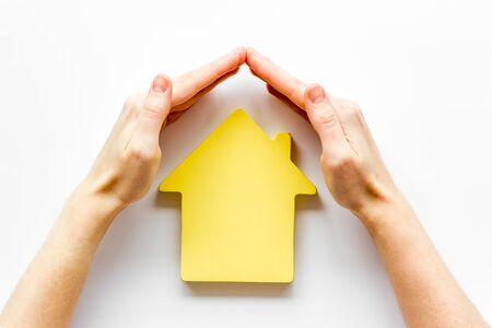 Property insurance concept. Hand defends house cutout on white background top view 版權商用圖片