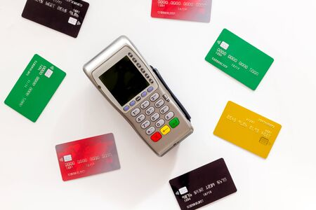 Bank terminal for payments among plastic cards on white background top-down