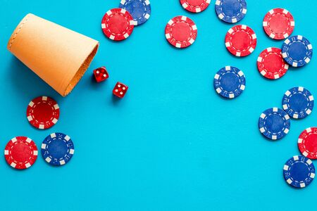 Poker frame. Chips and dices on blue background top-down copy space