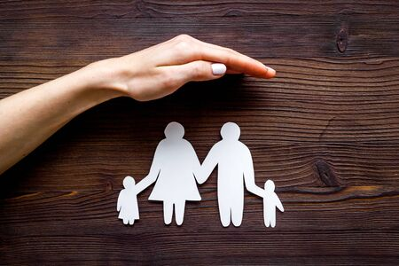 Health insurance concept. Family cutout under palms protect on dark wooden background top-down copy space