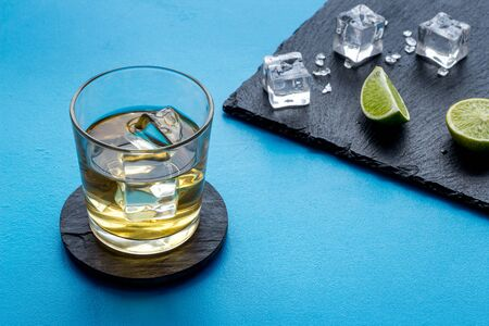 Whiskey near ice cubes on blue background copy space