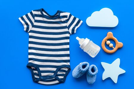 Blue bodysuit for baby boy near childrens accessories on blue background top-down Stock fotó