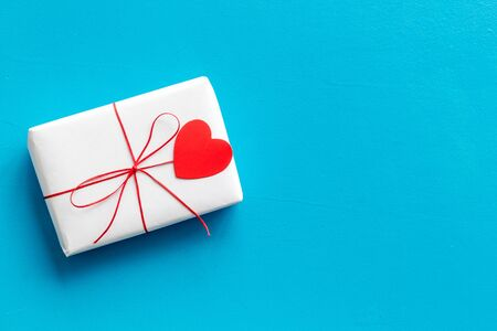 Valentines Day gift. Present box near paper hearts on blue background top-down copy space