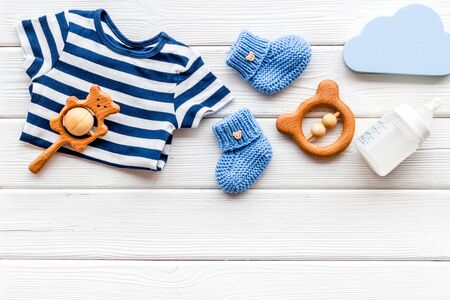 Baby background - blue color. Clothes and accessories for newborn boy on white wooden table top-down frame copy space