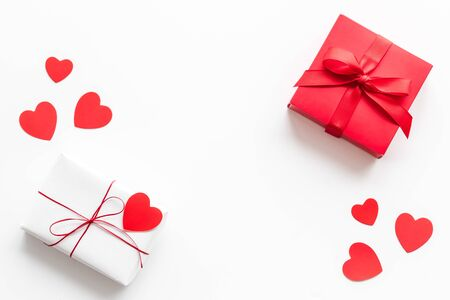 Present to a lover on Valentines Day. Gift boxes near paper hearts on white background top-down frame copy space