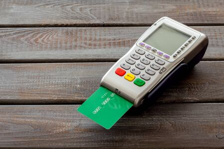 Bank terminal for payments and plastic card on dark wooden background.