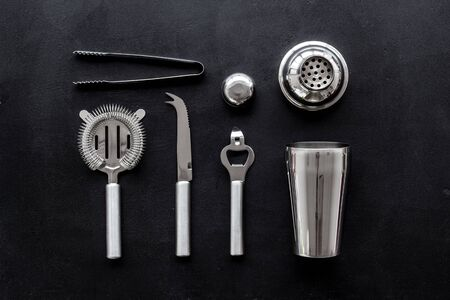 Bartender equipment set with shaker and strainer on black background top-down pattern.