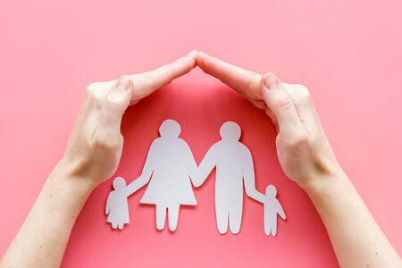 Live insurance concept. Family silhouette under palm on pink background top-down.