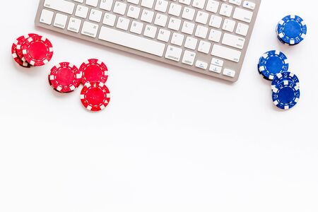 Gambling, online games. Chips near keyboard on white background top-down copy space Banque d'images