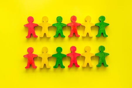 Team work, teambuilding concept. People cutouts on yellow background top-down pattern