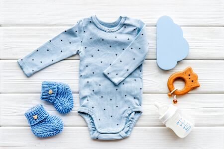 Blue bodysuit for baby boy near childrens accessories on white wooden background top-down