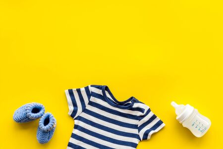 Baby background - blue color. Clothes and accessories for newborn boy on yellow table top-down frame.