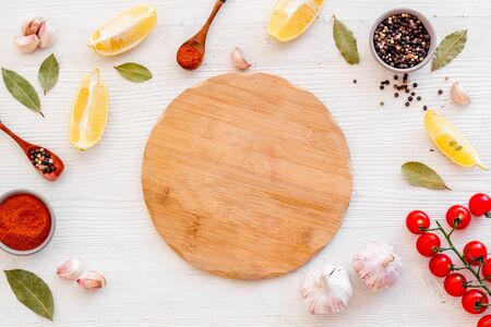 Mockup for menu. Cutting board near spices and vegetables on white background top-down