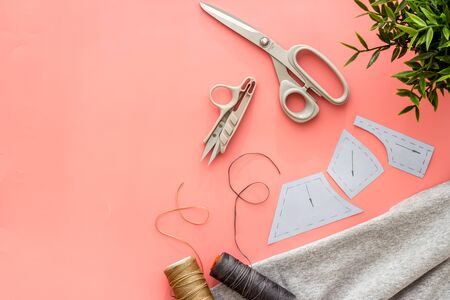 Sewing wokrshop. Textile, pattern, scissors, thread on pink background top-down copy space Reklamní fotografie