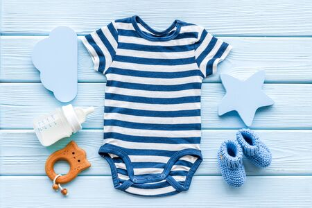 Blue bodysuit for baby boy near childrens accessories on blue wooden background top-down Stock fotó