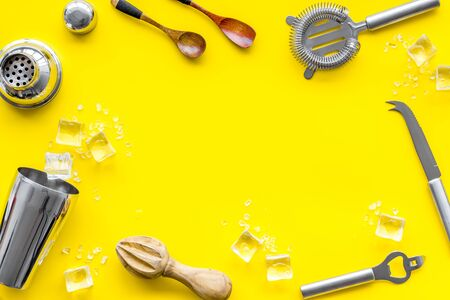 Bar utensil, tools - shaker, stainer - near ice cubes on yellow background top-down. Banque d'images - 138374541