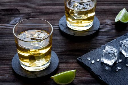 Whiskey near ice cubes on dark wooden background. Banque d'images - 138379761