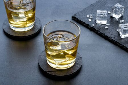 Whiskey near ice cubes on black background. Banque d'images - 138374902