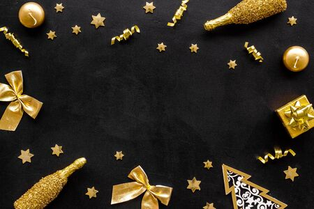 New Year mockup in gold color. Champagne bottle, present box, decoration, balls on black background top-down frame. Banque d'images - 138466848