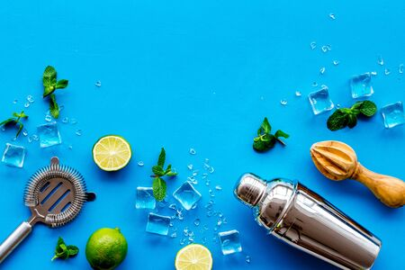 Bar background. Tools and ingredients for making cocktails. Shaker, lime, ice on blue background top-down. 스톡 콘텐츠