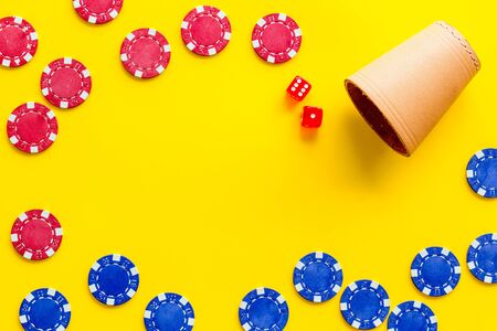 Poker frame. Chips and dices on yellow background top-down. Stock Photo