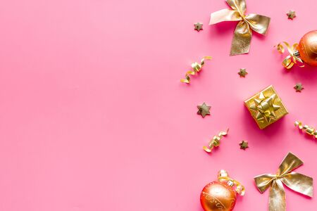 New Year decoration background - golden balls and bows on pink desk top-down frame. Banque d'images - 138467036