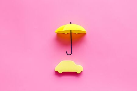 Car protection. Automobile toy under umbrella on pink background top-down copy space