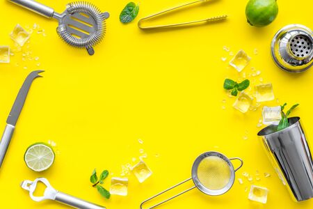 Bar background. Tools and ingredients for making cocktails. Shaker, lime, ice on yellow background top-down frame copy space