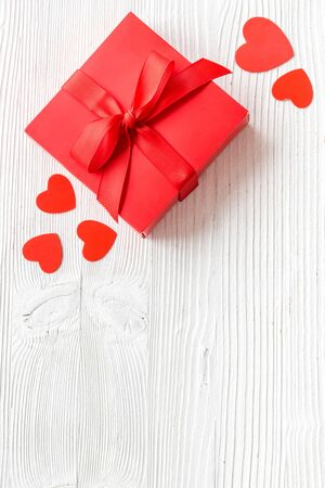 Gift to a sweetheart on Valentine's Day. Red present box near hearts on white wooden background top-down. Foto de archivo - 138467178