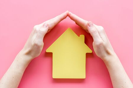 Property insurance concept. Hand defends house cutout on pink backgound top view. 版權商用圖片
